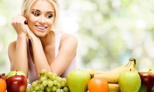 Beautiful smiling woman and fresh fruits